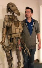"Collin Royster sizes up the ""Star Wars"" B1 battle droid he created using software and manufactured with a 3D plastic printer over 1,100 hours. Ohio Valley Art League Executive Director Jordyn Myracle, who curated the upcoming Collin Royster: Out of His Mind exhibit at the Preston Arts Center, particularly admires who realitically he weathers and distresses his creation to reflect the toil of the battles they wage in science fiction movies and videogames."