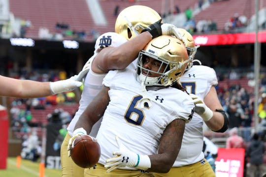 Fighting Irish running back Tony Jones Jr. (6) is congratulates by offensive lineman Aaron Banks (69) after scoring a touchdown during the first quarter against the Stanford Cardinal at Stanford Stadium.