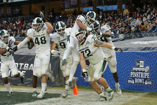 Dec 27, 2019; Bronx, New York, USA; Michigan State defensive tackle Mike Panasiuk (72) celebrates his interception return for a touchdown against the Wake Forest Demon Deacons with teammates during the first quarter of the Pinstripe Bowl at Yankee Stadium. Mandatory Credit: Brad Penner-USA TODAY Sports