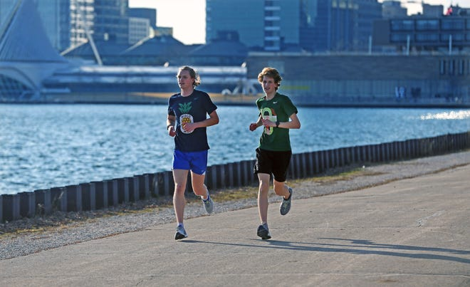 """With the city skyline to their backs, brothers Christian, left, 20, and Joshua Lesac, 16, of Milwaukee take advantage of the unusual warm weather at the lakefront on Thursday. """"It's amazing. I don't think I can ever imagine when it's been so warm after Christmas,"""" said Christian. The brothers were hoping to get in a five-mile run."""