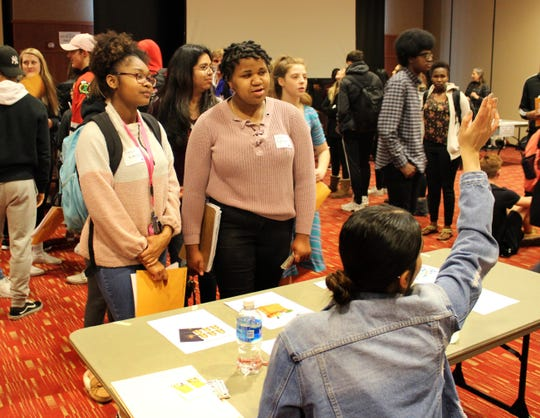 Cardinal Stritch University freshman Cierra Jones and Lakira Grant wait in line for an interpreter during their final exam, a simulation of the lives of immigrants in Milwaukee.