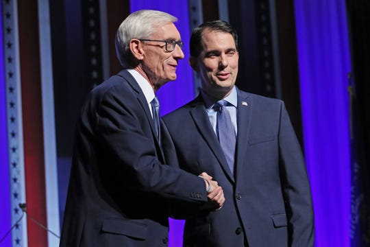 Democrat Tony Evers, left, and then-Gov. Scott Walker, a Republican, shake hands during a media event before the start of a 2018 gubernatorial debate.