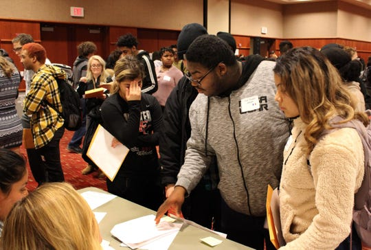 A student stands in frustration as she awaits her turn at a station in the immigration simulation at Cardinal Stritch University. All freshman at the university participated in the activity, which was a part of their final exam.