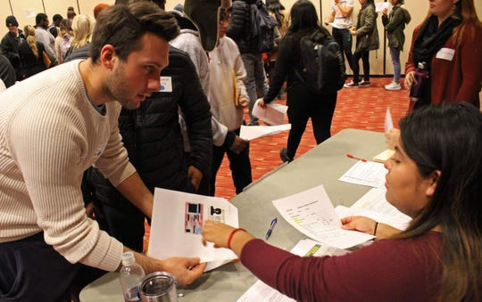 A student participating in Cardinal Stritch University's laberinto immigration simulation asks a question at one of the stations.