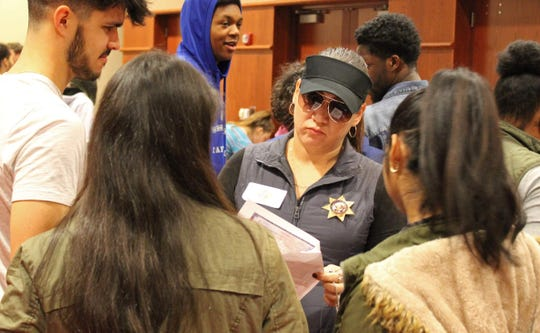 Yanelis Rodriguez, the executive assistant to the vice president of academic affairs, inspects students' identification in her role as a sheriff's deputy during Cardinal Stritch University's simulation on immigration experiences.