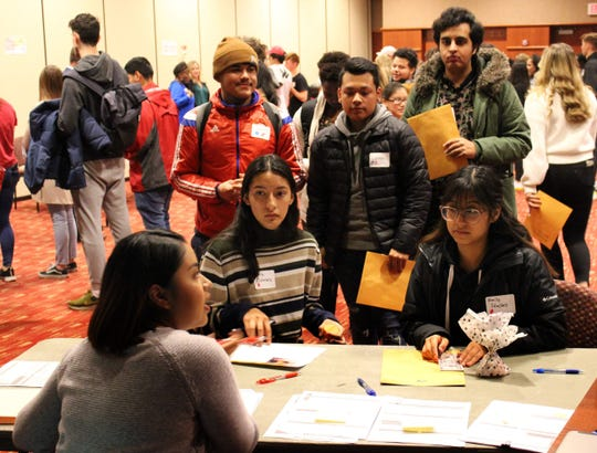 """Students gather at a station during Cardinal Stritch's """"laberinto"""" simulation about immigration. With few managers at the tables and 150 students in need of help, lines grew longer as the simulation progressed."""