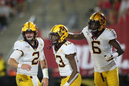 Minnesota wide receivers Rashod Bateman (13) and Tyler Johnson (6) celebrate with quarterback Tanner Morgan (2) after catching a touchdown against Fresno State on Sept. 7, 2019.