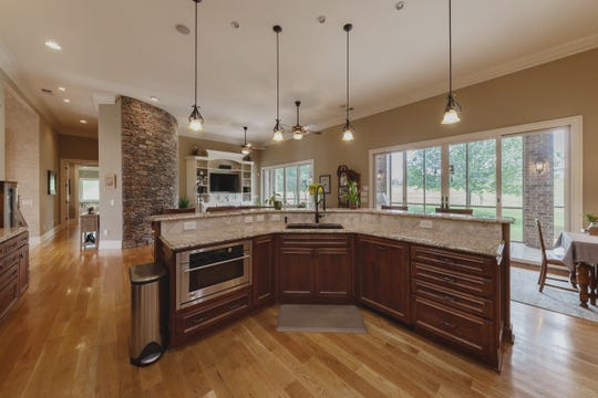 The kitchen has a six-burner and griddle gas stove with double ovens. A butler's pantry has a prep sink and another oven. There is a separate large, walk-in pantry.