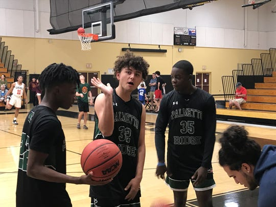 From left, Palmetto Ridge's Derwin Damys, Hayden Migliazzo and Kamar Titus return to the bench during warm-ups before the Bears' game against Seminole at the Kelleher Firm Gulfshore Holiday Hoopfest on Friday.