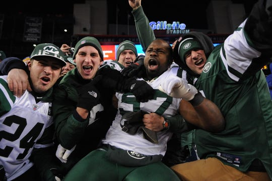 Jets' Bart Scott (57) jumps into the crowd after defeating the New England Patriots 28-21 at Gillette Stadium in 2011.