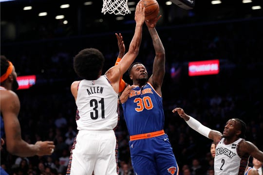 Brooklyn Nets center Jarrett Allen (31) defends as New York Knicks forward Julius Randle (30) shoots with Nets forward Taurean Prince (2) watching during the first half of an NBA basketball game, Thursday, Dec. 26, 2019, in New York. (AP Photo/Kathy Willens)