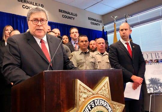 In this Nov. 12, 2109 file photo U.S. Attorney General William Barr, left, with other federal and officials, announces that nearly 330 fugitives suspected of violent crimes have been arrested as part of a crime-fighting initiative in New Mexico, at a news conference at the office of the Bernalillo County Sheriff in Albuquerque. New Mexico Democrats pushed forward a progressive agenda as the booming oil industry made headlines in 2019 with record revenues for the state's coffers.