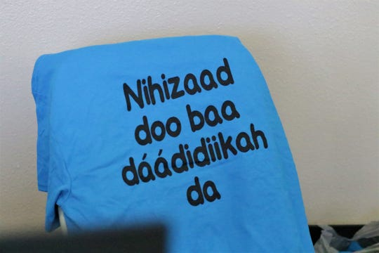 """The phrase, """"We'll never lose our language,"""" in Navajo appears on the back of a Diné Language Teachers Association T-shirt at the association's conference in Farmington on Oct. 17, 2019."""