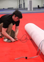 Suburban Collection Showplace employee Ian Morley gets the red carpeting ready Dec. 20 for the Southeast Michigan Auto Show.