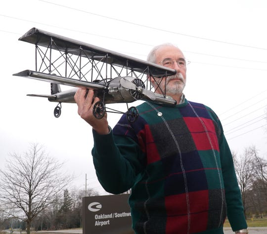 Retired Delta pilot David P. Schilstra gamely poses with a tin model biplane at the Oakland/Southwest Airport in New Hudson on Dec. 27, 2019. On that day he received the Wright Brothers Master Pilot Award for more than 50 years of safe, incident-free flying for carriers and privately.