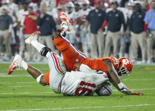 Ohio State Buckeyes quarterback J.T. Barrett (16) is knocked to the ground by Clemson Tigers defensive end Clelin Ferrell (99) during the second quarter of the College Football Playoff semifinal game in the PlayStation Fiesta Bowl on Dec. 31, 2016 at University of Phoenix Stadium in Glendale, Arizona.