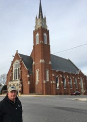 Eric Lowe stands on East Market Street with the Fourth UM Church bell tower, clocks and steeple behind him.