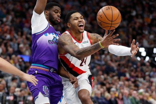 Utah Jazz guard Emmanuel Mudiay, left, and Portland Trail Blazers guard Kent Bazemore (24) battle during the first quarter of an NBA basketball game, Thursday, Dec. 26, 2019, in Salt Lake City.