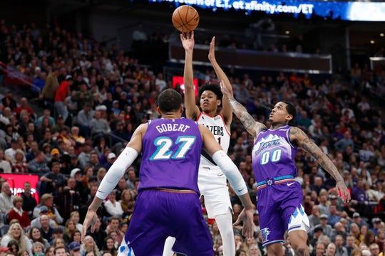 Portland Trail Blazers guard Anfernee Simons (1) shoots against Utah Jazz center Rudy Gobert (27) and guard Jordan Clarkson (00) during the second quarter of an NBA basketball game, Thursday, Dec. 26, 2019, in Salt Lake City.