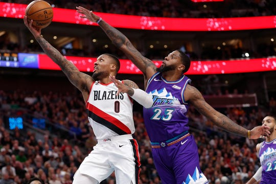 Portland Trail Blazers guard Damian Lillard (0) drives past Utah Jazz forward Royce O'Neale (23) during the second quarter of an NBA basketball game, Thursday, Dec. 26, 2019, in Salt Lake City.