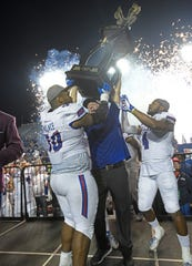 Louisiana Tech head coach Skip Holtz and his players celebrate after beating Miami in the Walk-On's Independence Bowl.