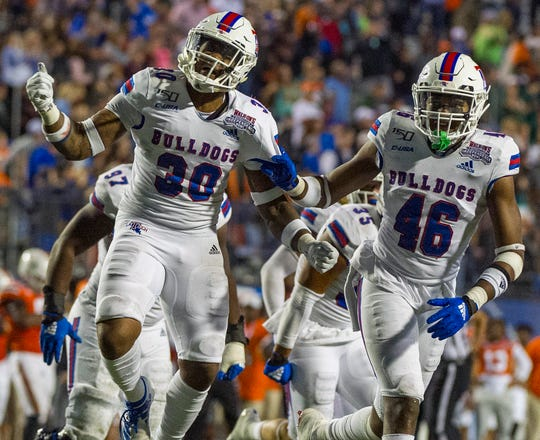 Louisiana Tech cornerback Aaron Roberson (30) and linebacker Ezekiel Barnett (46) celebrate during their team's Independence Bowl win over Miami.