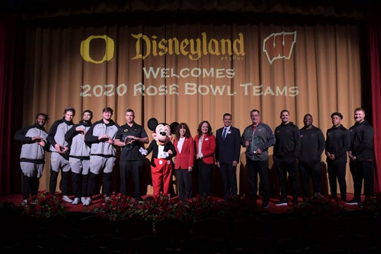 Oregon Ducks and Wisconsin Badgers players pose during the Disneyland Rose Bowl Team Visit, Thursday, Dec. 26, 2019, in Anaheim, Calif .From left: Oregon defensive tackle Jordon Scott, quarterack Justin Herbert, lineman Calvin Throckmorton and coach Mario Cristobal, Mickey Mouse, Pasadena Tournament of Rose president Laura Farber, Disneyland Park vice president Kris Theiler, Disney ambassador Rafa Barron, Wisconsin coach Paul Chryst, linebackers Zack Baun and Chris Orr, running back Jonathan Taylor and lineman Tyler Biadasz.