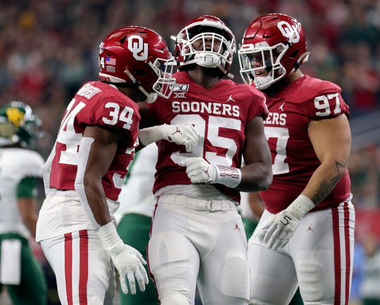 Oklahoma linebacker David Ugwoegbu (34) and defensive lineman Isaiah Thomas (95) and defensive lineman Marquise Overton (97) celebrate with Nik Bonitto during the second half against Baylor the 2019 Big 12 Championship Game at AT&T Stadium.