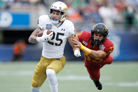 Braden Lenzy (25) of the Notre Dame Fighting Irish runs with the ball after catching a pass against Braxton Lewis (33) of the Iowa State Cyclones in the first half of the Camping World Bowl at Camping World Stadium on Dec. 28, 2019 in Orlando, Florida.