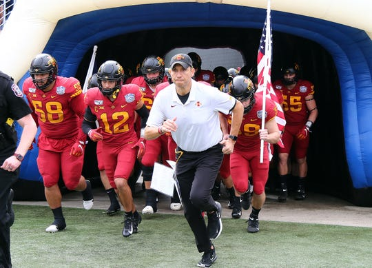 Iowa State Cyclones head coach Matt Campbell runs out with teammates prior to the game against the Notre Dame Fighting Irish at Camping World Stadium.
