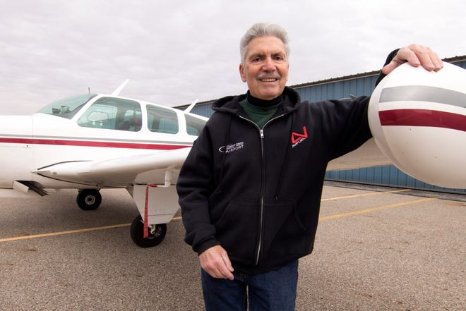 In this Dec. 13, 2019 photo, Mario Pecchia, an employee at the Spencer J. Hardy Airport in Howell, Mich., has been honored for an FAA Wright Brothers Master Pilot award. He stands at the wing of a 1967 Beechcraft Bonanza owned by his friend Ray Blach, outside a hangar at the airport. (Gillis Benedict/Livingston County Daily Press & Argus via AP)