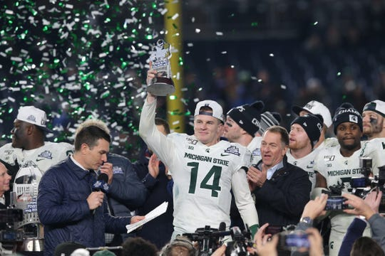 Brian Lewerke holds up the MVP trophy after defeating Wake Forest at Yankee Stadium.