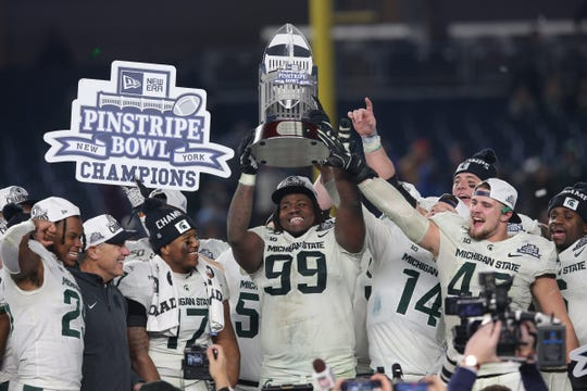 Michigan State defensive tackle Raequan Williams (99) and defensive end Kenny Willekes (48) celebrate with the Pinstripe Bowl trophy after defeating Wake Forest, 27-21, at Yankee Stadium, Friday, Dec. 27, 2019, in New York.