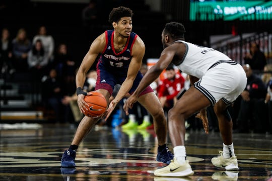Detroit Mercy Titans forward Alonde LeGrand (13) dribbles against Oakland Golden Grizzlies forward Xavier Hill-Mais (14) during the first half at Oakland University in Auburn Hills, Saturday, Dec. 28, 2019.