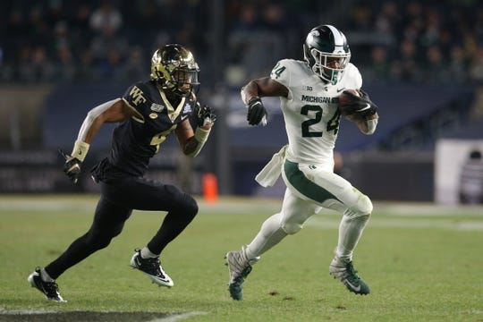 Michigan State running back Elijah Collins runs past Wake Forest defensive back Amari Henderson during the third quarter of the Pinstripe Bowl at Yankee Stadium, Friday, Dec. 27, 2019, in New York.