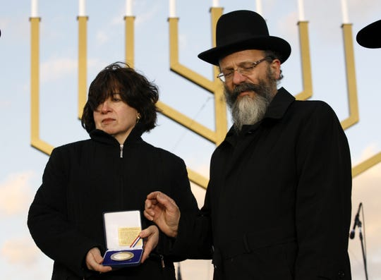 Rabbi Nachman and Frieda Holtzberg receive a medal during the lighting ceremony of the National Hanukkah Menorah, at the Ellipse in Washington Sunday Dec. 21, 2008, marking the beginning of the celebration of the Hanukkah.