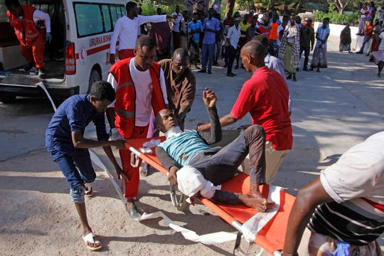 Medical personnel carry a civilian who was wounded in suicide car bomb attack at check point in Mogadishu, Somalia, Saturday, Dec, 28, 2019.