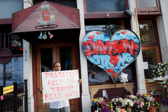 Damon Smith presents a message to President Donald Trump beside a makeshift memorial for the slain and injured victims of a mass shooting that occurred in the Oregon District early Sunday morning, Wednesday, Aug. 7, 2019, in Dayton, Ohio.