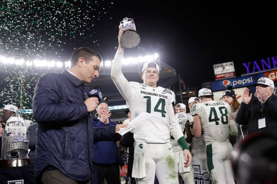 Michigan State's Brian Lewerke holds the Most Valuable Player trophy.