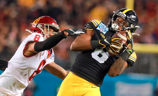 Iowa's Ihmir Smith-Marsette, right, catches a long pass as USC's Chris Steele defends during the third quarter of the Holiday Bowl.
