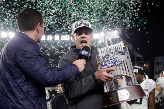 Michigan State head coach Mark Dantonio, right, speaks while holding the Pinstripe Bowl trophy.