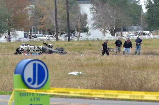 Investigators look over the site of a plane crash near Feu Follet Road and Verot School Road in Lafayette, La., Saturday, Dec. 28, 2019.