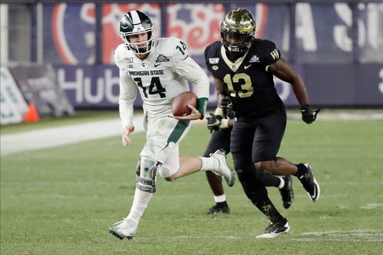 Michigan State quarterback Brian Lewerke runs away from Wake Forest defensive lineman Manny Walker during the second half.