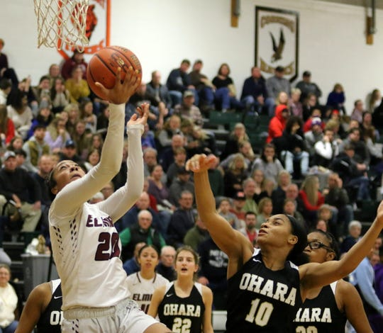 Elmira's Zaria DeMember-Shazer goes up for a reverse layup as Cardinal O'Hara's Courtney McClaney (10) defends during the Hawks' 56-51 win  over the Express in the girls division of the Josh Palmer Fund Elmira Holiday Inn Classic on Dec. 27, 2019 at Elmira High School.