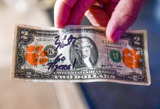 "Dean ""The Hat"" Cox, a Clemson fan, shows his Tiger paw stamped two dollar bill at the Arizona Clemson Club and Clemson Alumni Association party at K O'Donnell's Bar and Grill in Scottsdale, Arizona Friday December 27, 2019. Clemson fans mark their ""Tiger Two's"" with orange paws from a stamp pad, and spend them to give businesses on the road the idea their economic impact."