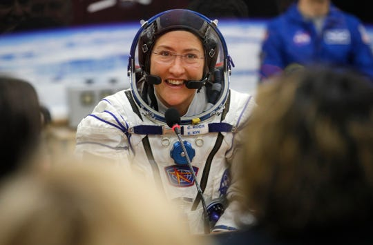 FILE - In this Thursday, March 14, 2019 file photo, U.S. astronaut Christina Koch, member of the main crew of the expedition to the International Space Station (ISS), speaks with her relatives through a safety glass prior the launch of Soyuz MS-12 space ship at the Russian leased Baikonur cosmodrome, Kazakhstan.  Koch will set a new record Saturday, Dec. 28, for the longest single spaceflight by a woman, breaking the old mark of 288 days with about two months left in her mission. Koch, a  40-year-old electrical engineer arrived at the International Space Station on March 14. She broke the record previously set by former space station commander Peggy Whitson in 2016-2017. (AP Photo/Dmitri Lovetsky, Pool)