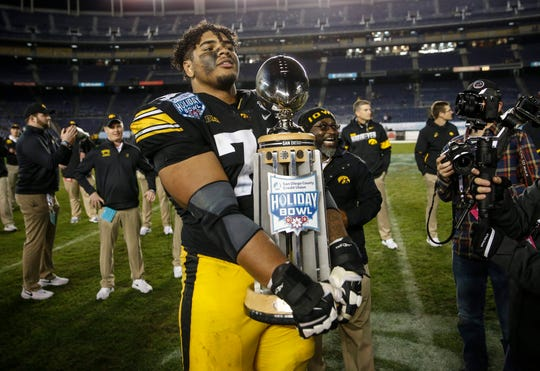 Iowa junior right tackle Tristan Wirfs holds the Holiday Bowl trophy after the Hawkeyes beat USC, 49-24, on Friday, Dec. 27, 2019, at the SDCCU Stadium in San Diego, Calif.