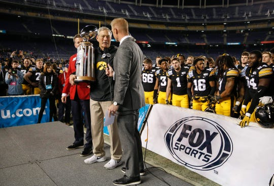 Kirk Ferentz is presented with the Holiday Bowl trophy from lead Fox Sports analyst Joel Klatt after the Hawkeyes demolished USC, 49-24, on Dec. 27.