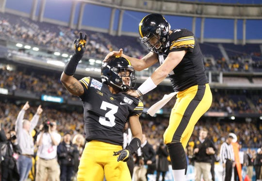 Tyrone Tracy Jr. is met by excited quarterback Nate Stanley after scoring Iowa's first touchdown of a high-powered night.