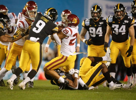 Iowa senior defensive back Michael Ojemudia, right, and Geno Stone team up to tackle USC receiver Vavae Malepeai in the first quarter during the Holiday Bowl on Friday, Dec. 27, 2019, at the SDCCU Stadium in San Diego, Calif.